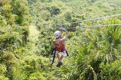 Mujer que va en una aventura del zipline de la selva Foto de archivo libre de regalías