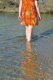 Mujer que vadea a través de la agua de mar Fotografía de archivo libre de regalías