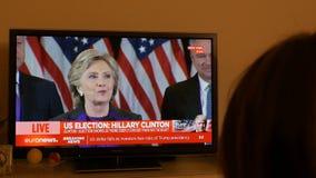Mujer que ve la TV después de las elecciones de los E.E.U.U. que escuchan el discurso de Hillary Clinton almacen de video