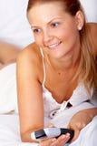 Mujer que ve la TV en cama Foto de archivo libre de regalías