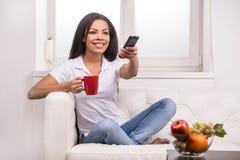 Mujer que ve la TV en casa y que sostiene un teledirigido foto de archivo libre de regalías