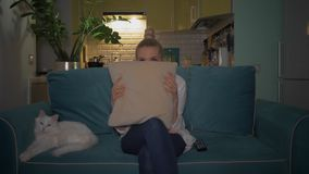 Mujer que ve la TV en el pa?s Muchacha que ve la TV el sentarse en el sofá con su gato Muchacha que mira una película y una ocult metrajes