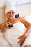 Mujer que ve la TV en su cama Fotos de archivo