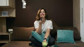 Mujer que ve la TV y que come una sentada de Apple en la cama en el dormitorio Canales de los interruptores con teledirigido almacen de video