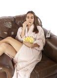 Mujer que ve la TV y que come las palomitas Imagenes de archivo