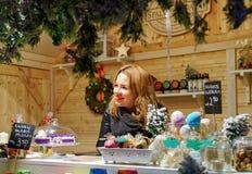 Mujer que vende el jabón hecho a mano en el mercado Lituania de la Navidad de Vilna Foto de archivo libre de regalías