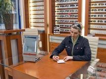 Mujer que vende gafas. Imagen de archivo libre de regalías