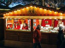 Mujer que vende hogares miniatura en el mercado de la Navidad Imagen de archivo