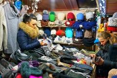 Mujer que vende la diversa ropa caliente en el mercado de la Navidad de Vilna Imagenes de archivo