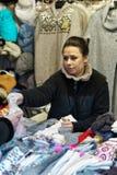 Mujer que vende la ropa caliente en el mercado de la Navidad de Vilna Foto de archivo