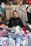 Mujer que vende la ropa caliente en el mercado de la Navidad de Vilna durante advenimiento Foto de archivo libre de regalías