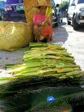 Mujer que vende las hojas de la palma y del coco fuera de una iglesia Fotografía de archivo libre de regalías
