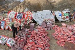 Mujer que vende las piedras de Mani con el mantra budista OM Mani Padme Hum grabado en tibetano en Yushu, China Fotografía de archivo libre de regalías