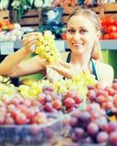 Mujer que vende las uvas en el mercado Imagen de archivo