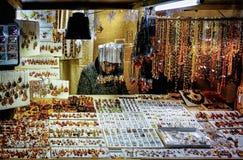 Mujer que vende los adornos ambarinos en mercado de la Navidad de Riga Fotos de archivo