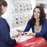 Mujer que vende un teléfono celular Foto de archivo libre de regalías