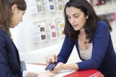 Mujer que vende un teléfono celular Fotos de archivo libres de regalías
