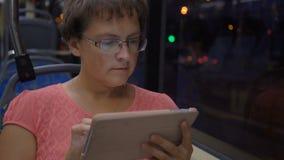 Mujer que viaja en la ciudad en autobús Ella usando la almohadilla táctil durante el viaje almacen de video