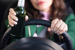 Mujer que viaja por el coche que sostiene la botella de cerveza foto de archivo libre de regalías