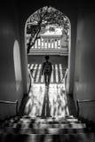 Mujer que viene abajo las escaleras debajo de un pórtico con luz del sol hermosa y sombra grande Imagen de archivo libre de regalías