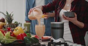 Mujer que vierte el smoothie anaranjado a un vidrio grande, desayuno en un diseño de la cocina del módem, par de la salud junto a almacen de metraje de vídeo