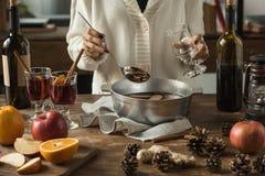 Mujer que vierte el vino reflexionado sobre hecho en casa fotografía de archivo libre de regalías