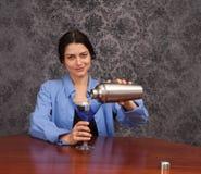 Mujer que vierte una bebida Imagen de archivo libre de regalías