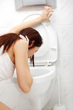 Mujer que vomita en el cuarto de baño. Imagenes de archivo