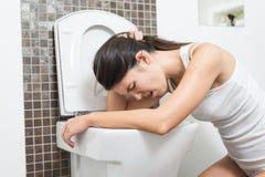 Mujer que vomita en la taza del inodoro Fotografía de archivo