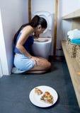 Mujer que vomita y que lanza para arriba el arrodillamiento en el piso del WC del retrete culpable después de comer la pizza Imagen de archivo