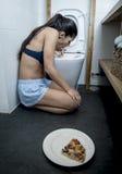 Mujer que vomita y que lanza para arriba el arrodillamiento en el piso del WC del retrete culpable después de comer la pizza Foto de archivo libre de regalías