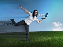 Mujer rápida con el ordenador portátil que hace SEO Imagen de archivo libre de regalías
