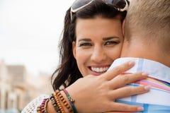 Mujer radiante hermosa que abraza a su novio Foto de archivo