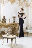 Mujer real rubia hermosa que se coloca cerca de la tabla retra en vestido de lujo magnífico con el vidrio de vino en su mano Fotos de archivo