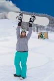 Mujer rechoncha joven en la actitud del ganador, aumentos su snowboard en el aire Foto de archivo libre de regalías