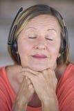 Mujer reclinada con música de los auriculares que escucha Imagen de archivo
