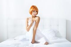 Mujer Redheaded en el dormitorio Imagen de archivo libre de regalías