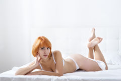 Mujer Redheaded en el dormitorio Fotos de archivo