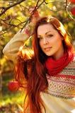 Mujer redheaded joven con el pelo recto largo en la manzana Garde Imagen de archivo