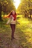 Mujer redheaded joven con el pelo recto largo en la manzana Garde Foto de archivo