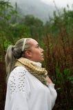 Mujer reflexiva bastante joven que mira para arriba en una montaña Imagen de archivo