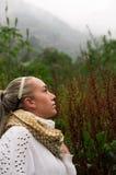 Mujer reflexiva bastante joven que mira para arriba en una montaña Imágenes de archivo libres de regalías
