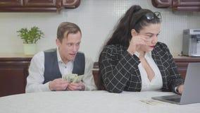Mujer regordeta confiada joven en vidrios en la tabla en la cocina que trabaja con el ordenador portátil Un hombre joven tímido d almacen de metraje de vídeo