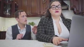 Mujer regordeta confiada joven en vidrios en la tabla en la cocina que trabaja con el ordenador portátil Un hombre joven tímido q metrajes