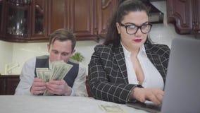 Mujer regordeta confiada joven en vidrios en la tabla en la cocina que trabaja con el ordenador portátil Un hombre joven tímido q almacen de video