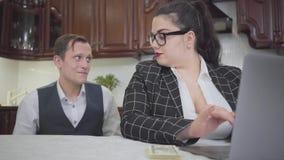 Mujer regordeta confiada joven linda del retrato en el funcionamiento de vidrios con el ordenador portátil en la tabla Hombre jov metrajes
