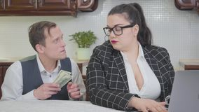 Mujer regordeta confiada joven que trabaja con el ordenador portátil en la tabla Un hombre joven tímido que pregunta a más dinero almacen de metraje de vídeo