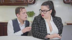 Mujer regordeta confiada joven que trabaja con el ordenador portátil en la tabla Un hombre joven tímido toca su hombro y ella lo  almacen de metraje de vídeo