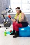 Mujer regordeta que ejercita con pesas de gimnasia Imagenes de archivo