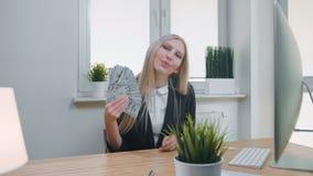 Mujer relajada con el dinero en oficina Hembra rubia joven elegante en el traje de negocios que se sienta en el escritorio con el metrajes